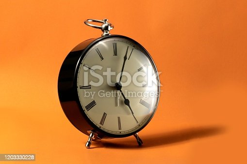 816405814 istock photo A portrait of a small old fashioned antique alarm clock with roman numbers on the dial on an orange background. The hands of the clock are pointing at a little past 5 o'clock. 1203330228