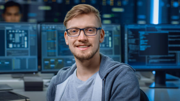 Porträt eines intelligenten und hübschen IT-Spezialisten, der gläsert, hinter ihm Personal Computer mit Bildschirmen zeigt Software-Programm mit Codierung Sprachschnittstelle im Rechenzentrum – Foto