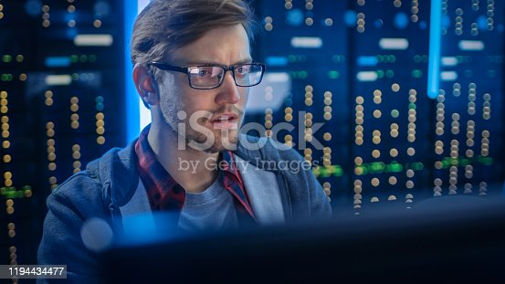 1154261912 istock photo Portrait of a Smart Focused Young Man Wearing Glasses Сoncentrated on a Desktop Computer. In the Background Technical Department Office with Functional Data Server Racks. 1194434477