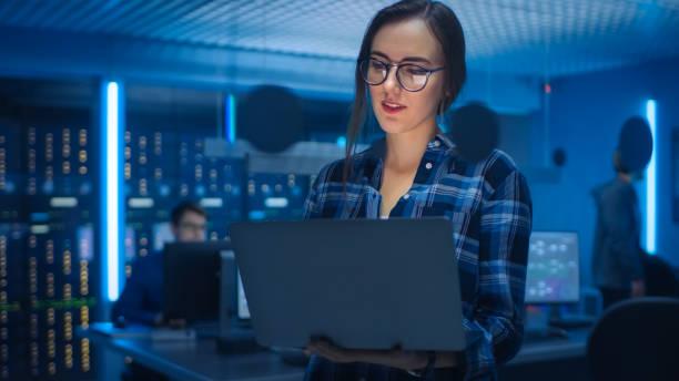Porträt einer smarten verführerischen jungen Frau, die eine Brille trägt, hält Laptop. Im Office der technischen Abteilung im Hintergrund mit Spezialisten für Arbeits- und Funktionsdatenserver-Racks – Foto