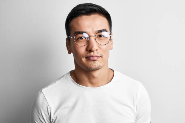 Portrait of a smart young Kazakh man in glasses and a T-shirt on a white background. Asian handsome student creative designer
