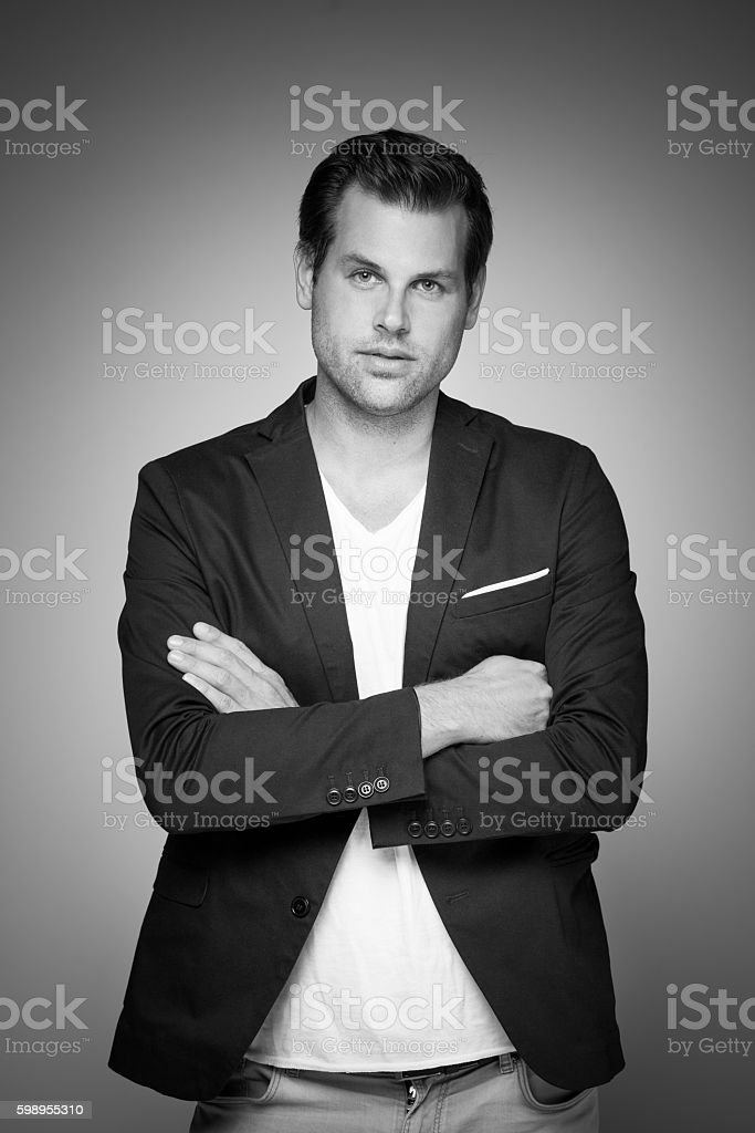 Portrait of a smart young man standing with arms crossed. Lizenzfreies stock-foto