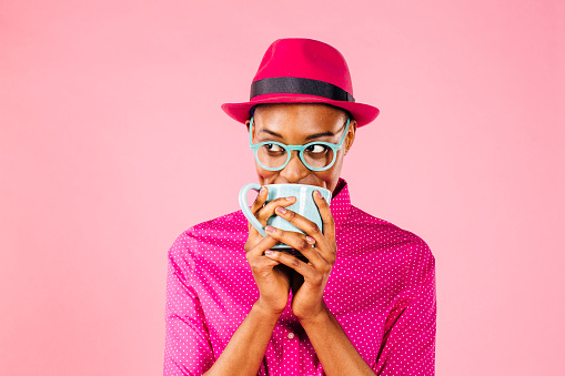 Portrait of a smart young woman with glasses drinking a coffee mug and looking to side, isolated on pink studio background