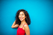 Portrait of a smiling Asian woman on a blue wall