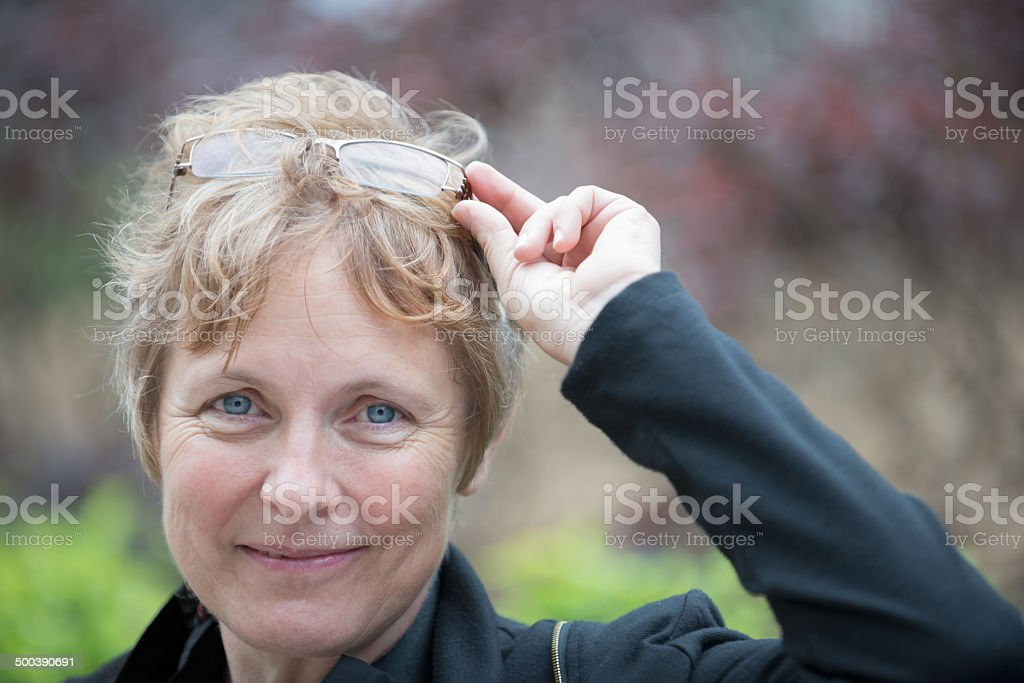 Portrait of a Smiling, Attractive, Mature Woman in a Park stock photo