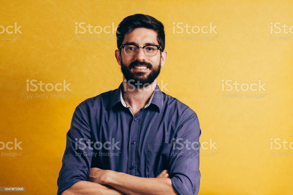 Portrait of a smiling bearded man in eyeglasses looking at camera isolated over yellow background royalty-free stock photo