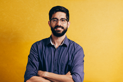 Portrait of a smiling bearded man in eyeglasses looking at camera isolated over yellow background