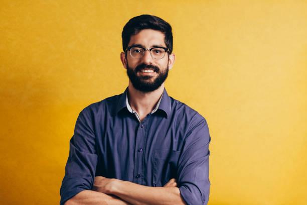 retrato de um sorridente barbudo homem de óculos, olhando para a câmera isolada sobre fundo amarelo - man portrait - fotografias e filmes do acervo