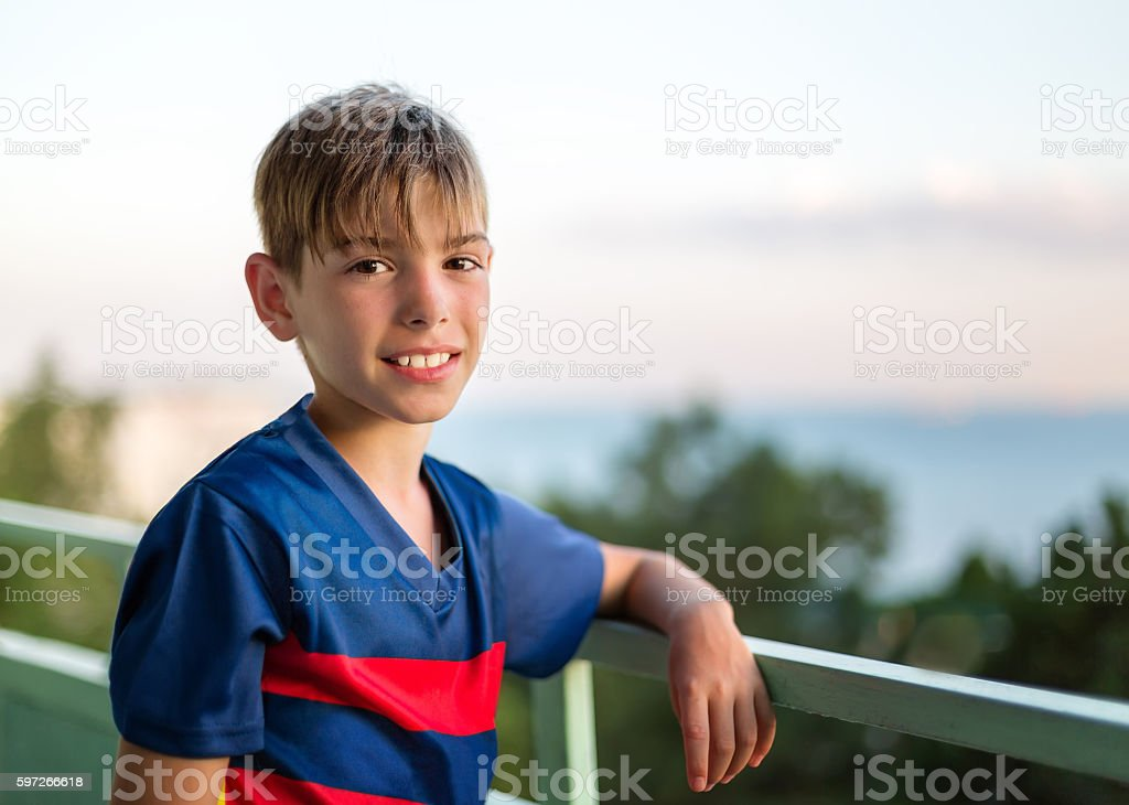 Portrait of a smiling boy against the sea at sunset royalty-free stock photo