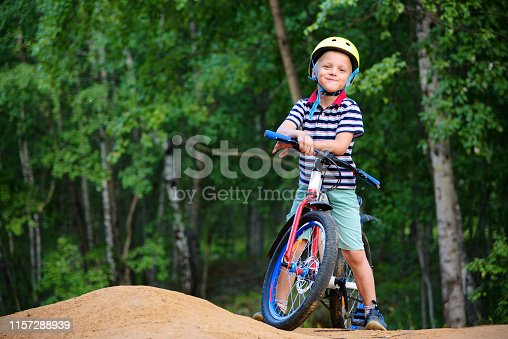 Boy cyclist standing in full growth near his bike against the background of the forest. Wearing a striped polo, blue shorts and a yellow helmet.