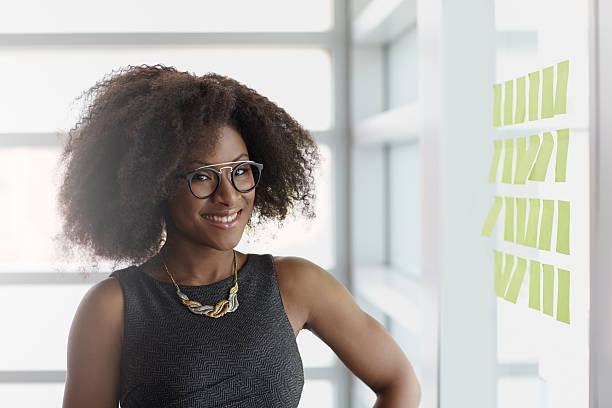 portrait of a smiling business woman with an afro in - authority stock photos and pictures