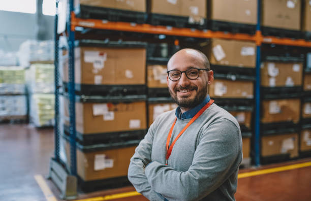 Portrait of a smiling businessman standing in corridor of warehouse stock photo