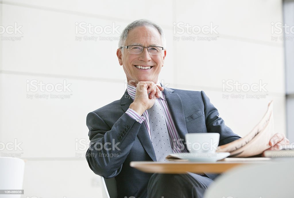 Portrait of a smiling businessman with coffee cup and newspaper sitting at coffee table royalty-free stock photo