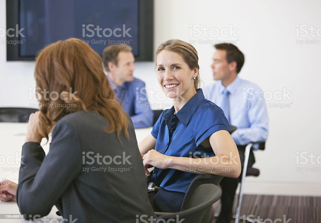 Portrait of a smiling businesswoman in meeting with colleagues in the background royalty-free stock photo