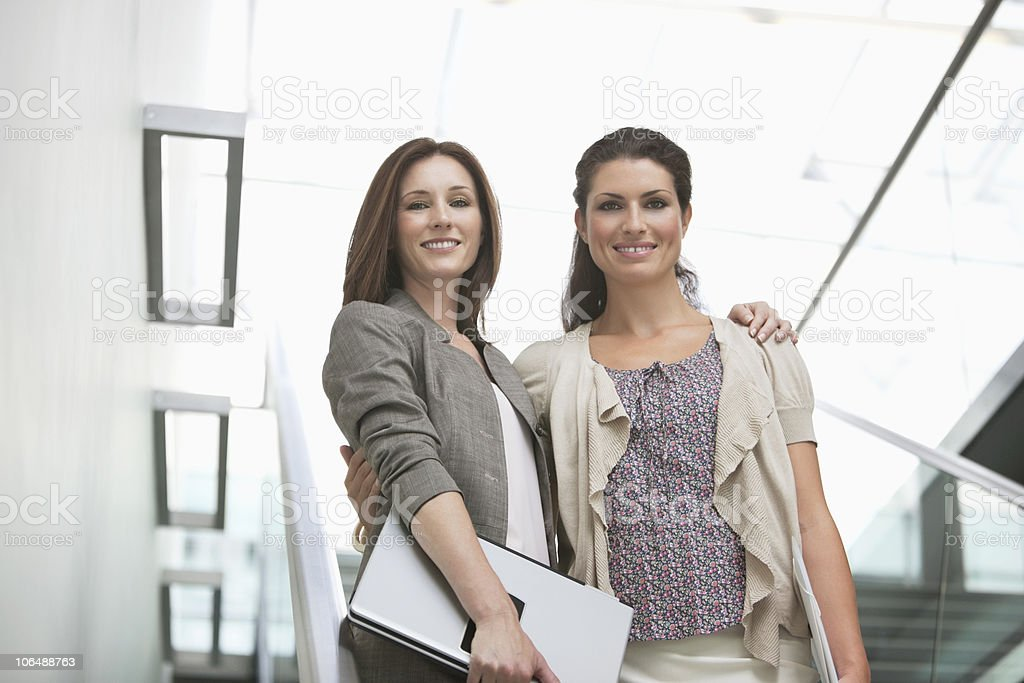 Portrait of a smiling businesswomen standing with arms around at office stock photo