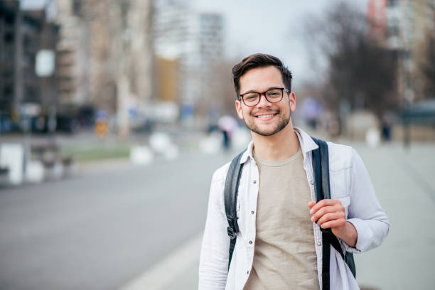 Portrait of a smiling casual man in urban background. Portrait of a smiling casual man in urban background. only young men stock pictures, royalty-free photos & images