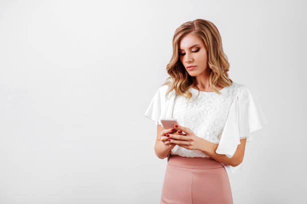 Portrait of a smiling casual woman holding smartphone stock photo