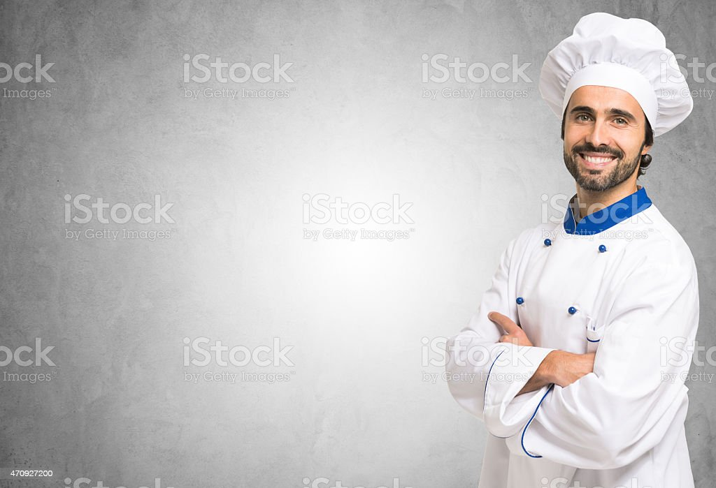 A portrait of a smiling chef with his arms folded stock photo