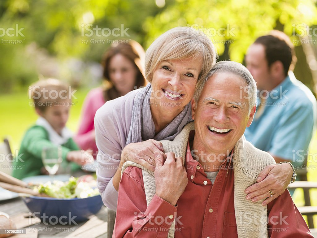 Portrait of a smiling couple on picnic with people in background stock photo