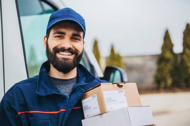 portrait of a smiling deliverer - postal worker стоковые фото и изображения