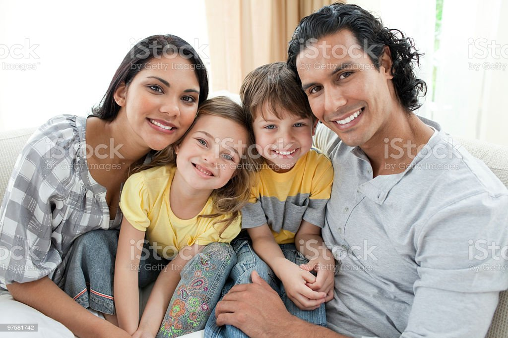 Portrait of a smiling family sitting on sofa royalty-free stock photo
