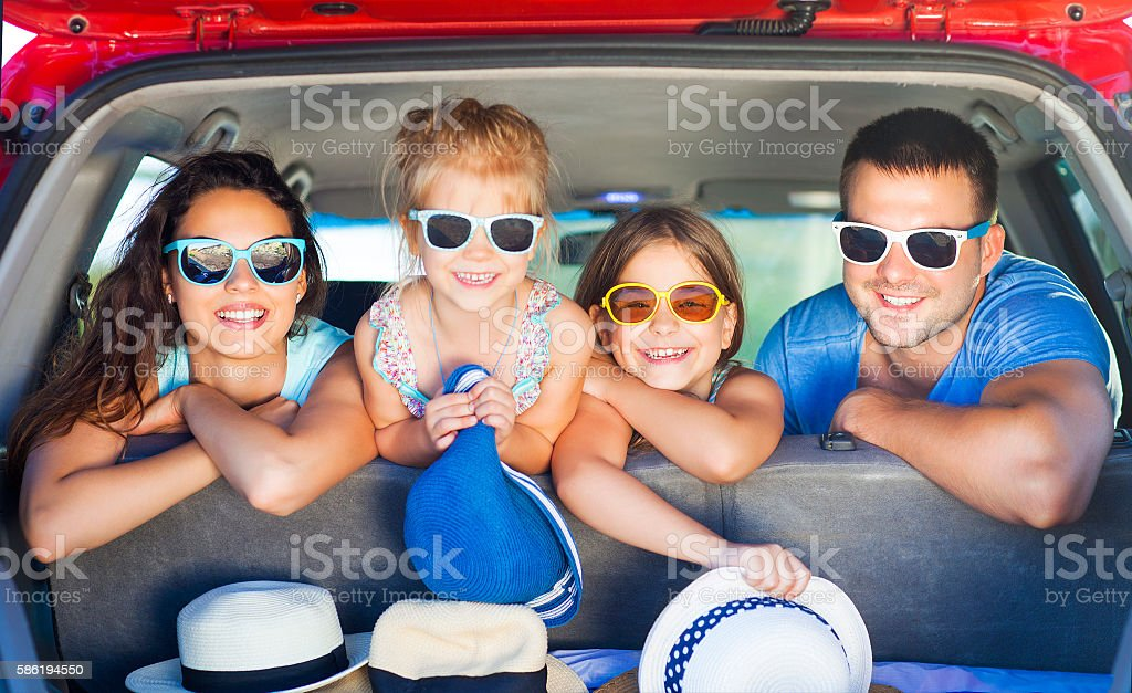 Portrait of a smiling family with two children at beach stock photo