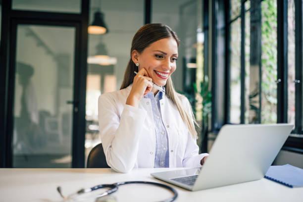 Retrato de una doctora sonriente mirando una computadora portátil en el consultorio médico. - foto de stock