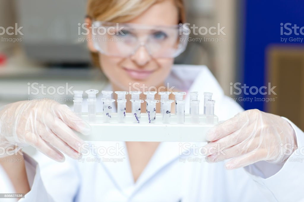 Portrait of a smiling female scientist holding different samples stock photo