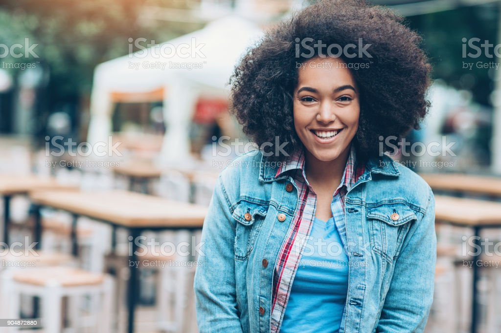 Portrait of a smiling girl outdoors in a sidewalk cafe stock photo