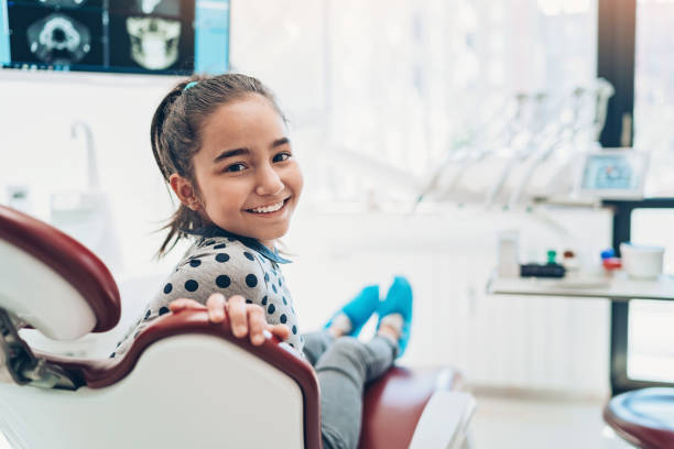 Portrait of a smiling girl sitting on a dentist's chair Girl patient sitting in the dentist's office dentist stock pictures, royalty-free photos & images