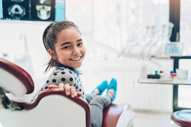 Porträt eines lächelnden Mädchens, das auf einem Zahnarztstuhl sitzt – Foto