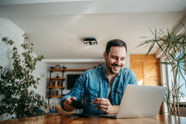 Retrato de un hombre guapo sonriente mirando la computadora portátil en la oficina en casa, sosteniendo anteojos y una taza de café. - foto de stock