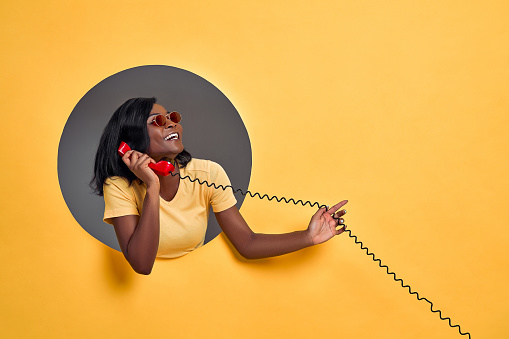 Portrait of a smiling happy afro american woman in sunglasses talking on retro telephone in a round hole circle in yellow background. Copy space.