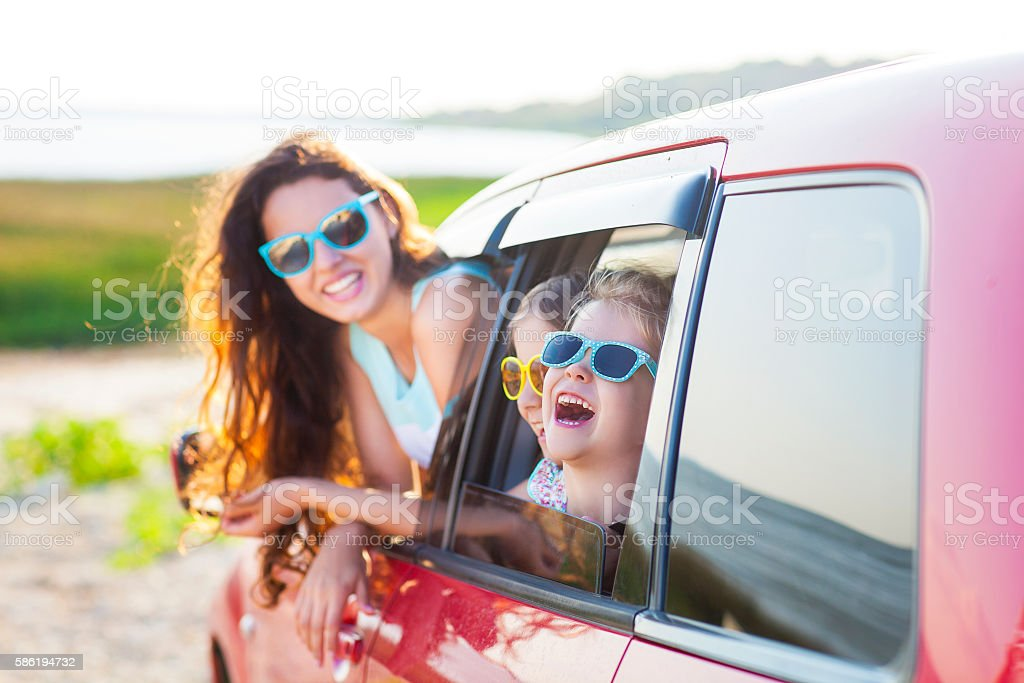 Portrait of a smiling happy mother with children at beach stock photo