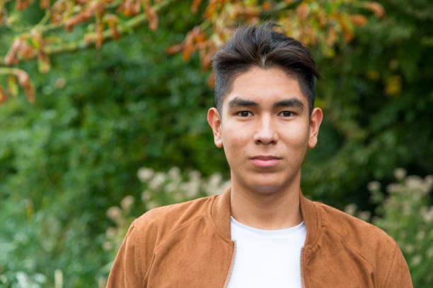 porträt eines lächelnden lateinamerikanischen jünglings mit eine braune wildlederjacke schuss außerhalb - kleidung amerikanischer ureinwohner stock-fotos und bilder
