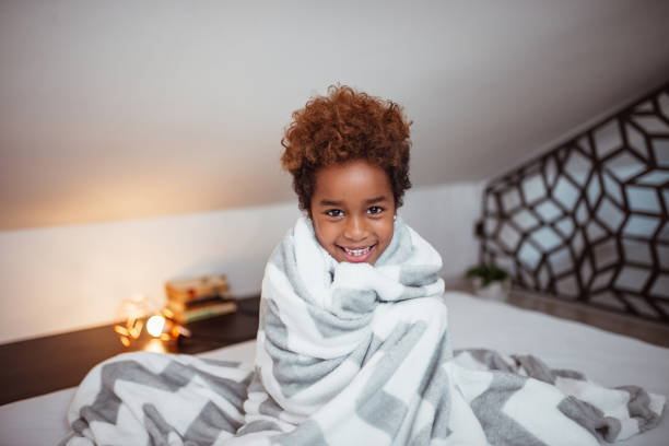 Portrait of a smiling little mixed-race girl with blanket sitting on bed and looking at camera Portrait of a smiling little mixed-race girl with blanket sitting on bed and looking at camera wrapped in a blanket stock pictures, royalty-free photos & images