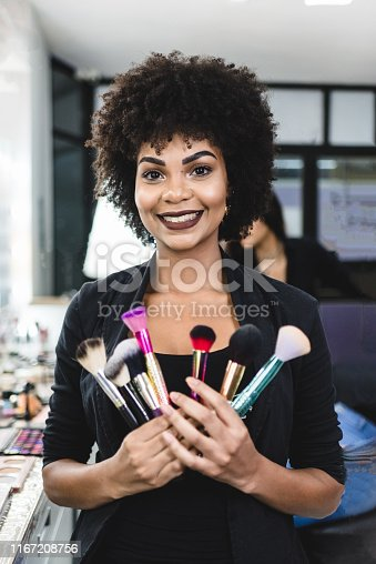 Portrait of a smiling makeup artist holding brushes