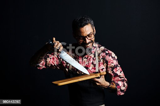 istock Portrait of a smiling man holding cutting board and butcher knife 980443292
