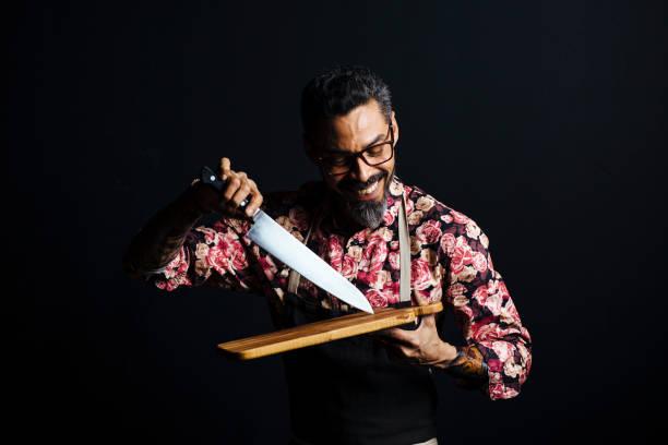 porträt von ein lächelnder mann mit schneidebrett und blockmesser - kochkunst stock-fotos und bilder
