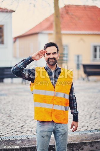 istock Portrait of a smiling man in an orange life jacket on the street salutes with a hand to his head. A young man with a beard jokes salute. A life jacket should be worn during a car accident. 931274688