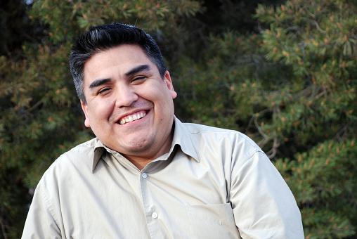A happy Hispanic man with a calm pine tree background