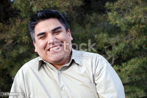 A happy Hispanic man with a calm pine tree background
