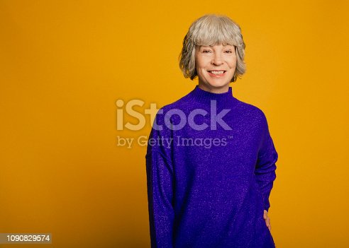 Portrait of a mature woman in front of a yellow background. She is wearing a purple sweater.
