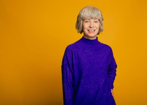 一個微笑的成熟的女人的肖像 - 有顏色的背景 個照片及圖片檔