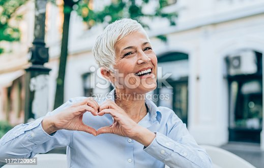 Beautiful smiling mature woman making heart shape with fingers.