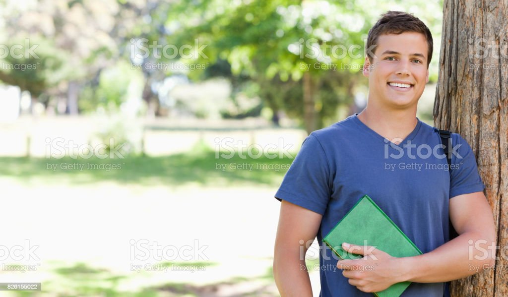 Portrait of a smiling muscled student holding a textbook stock photo