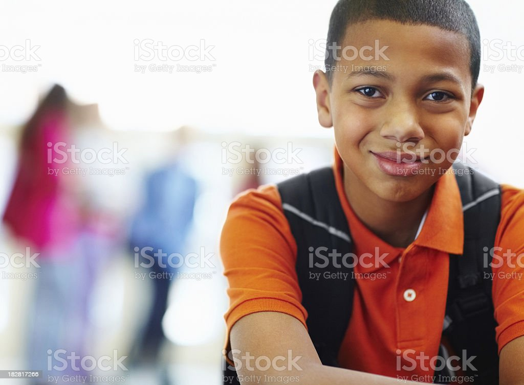 Portrait of a smiling schoolboy with friends in the background stock photo