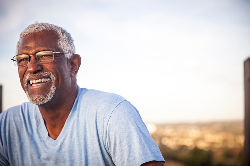 A senior black man smiling and laughing off in the distance