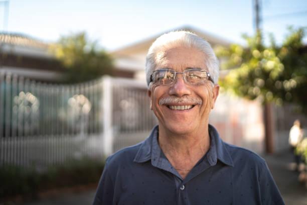 porträt eines lächelnden seniors auf der straße - einzelner senior stock-fotos und bilder