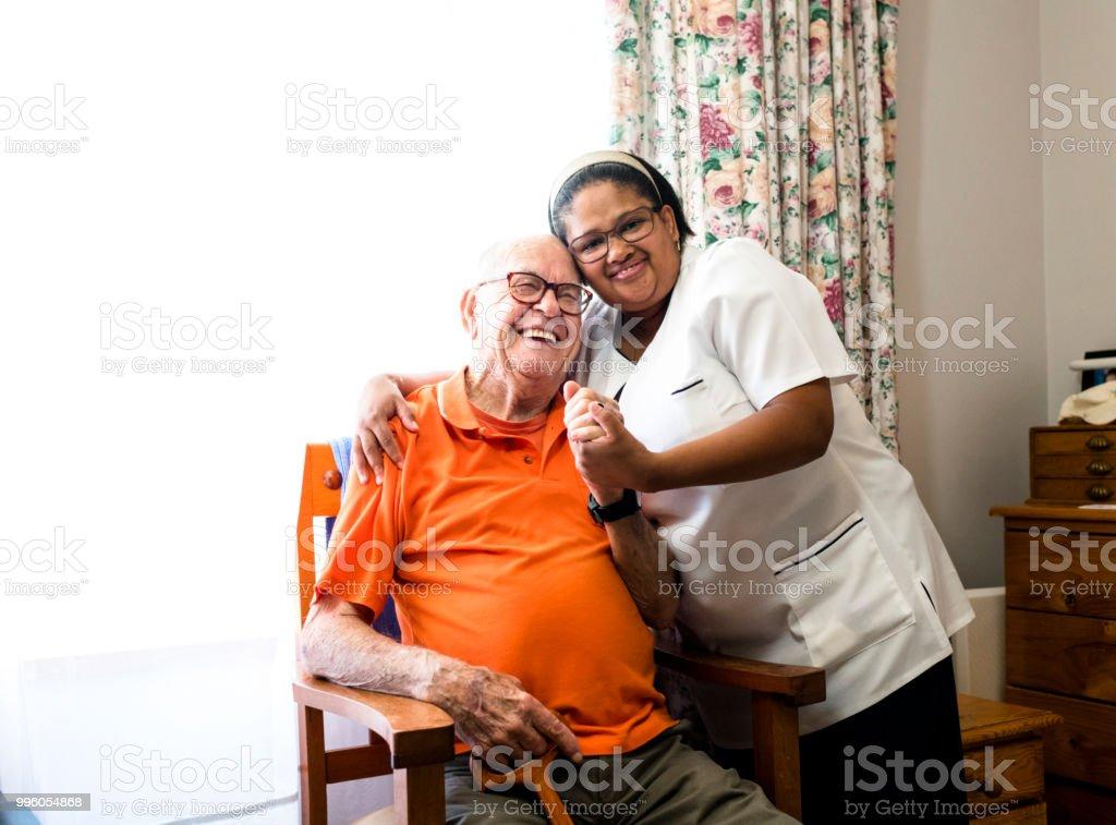 Porträt eines lächelnden senior woman und Krankenschwester umarmt – Foto